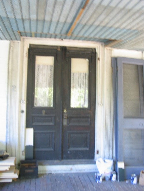 Victorian front doors in a lovely black show the distinct color palette repeated in the window trim